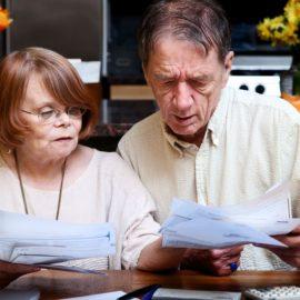 5690916 - senior couple at home organizing many bills